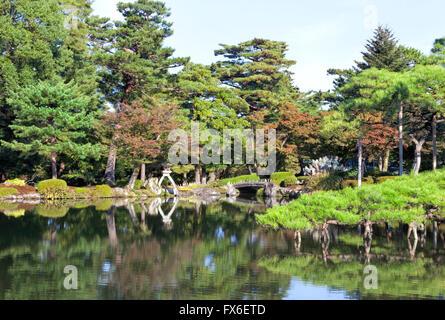 Japanese style garden park with stone bridge, lantern on a lake edge with green pine trees, autumn leaf trees - Stock Photo