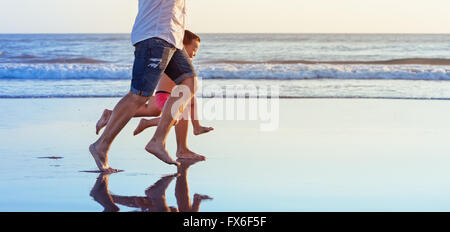 Barefoot legs in action. Happy family fun - parents with baby son running along edge of sea beach surf with sunset - Stock Photo