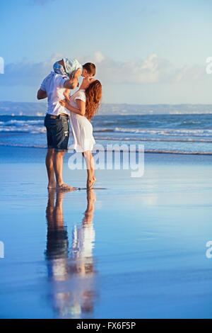 Happy family - baby son on father shoulders kiss mother, walk with fun along sunset sea surf on black sand beach. - Stock Photo