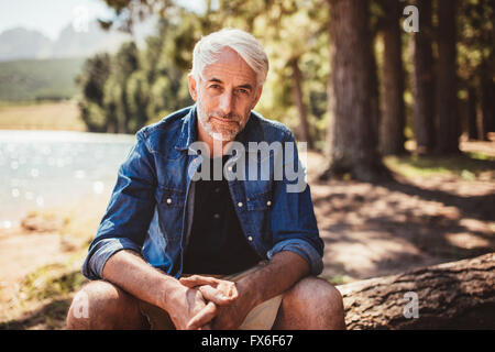 Portrait of mature man sitting near a lake staring at camera. Senior caucasian man relaxing on a log by the lake - Stock Photo