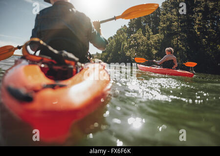 Portrait of mature woman kayaking in lake on a sunny day. Couple canoeing in a lake on  summer day. - Stock Photo