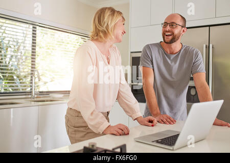Indoor shot of a happy couple standing at kitchen counter with laptop computer. Man and woman looking at each other - Stock Photo