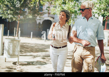 Senior couple on a vacation, roaming around in a foreign city. Man and woman walking in a town with camera and city - Stock Photo