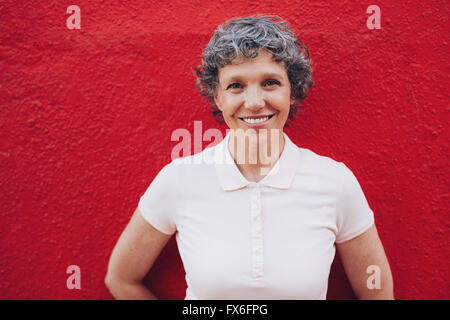 Portrait of senior woman standing against red background. Smiling mid adult female against red wall. - Stock Photo