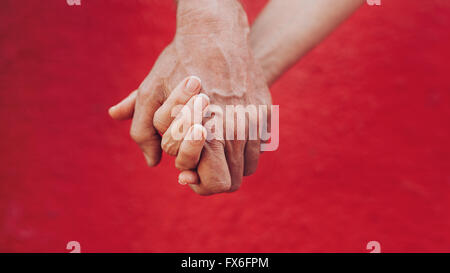 Close up of man and woman holding hands against red background. Affectionate couple holding hands. - Stock Photo