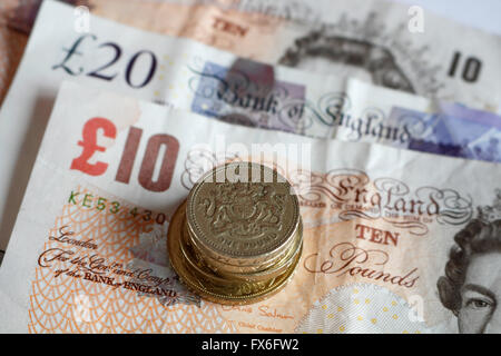 British banknotes and pile of pound coins - Stock Photo