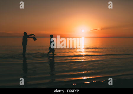 Silhouette of adult couple which costs in the sea and holds in hand footwear. - Stock Photo