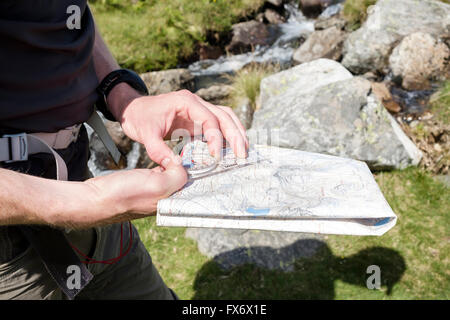 Hiker navigating the direction using holding a Harvey mountain map and Silva hiking compass to take a bearing in - Stock Photo