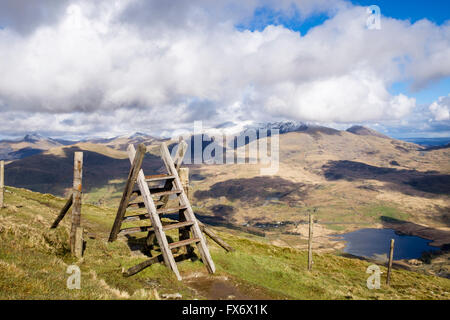 Ladder stile on path on Mynydd Drws-y-Coed on Nantlle Ridge with snowcapped Mount Snowdon in clouds in Snowdonia - Stock Photo