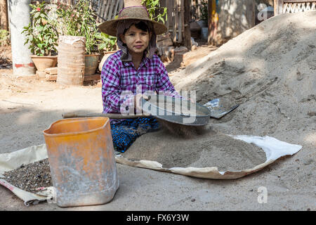 At New Bagan, an apprentice young woman preparing the mortar for workmen on a construction site (Myanmar). - Stock Photo