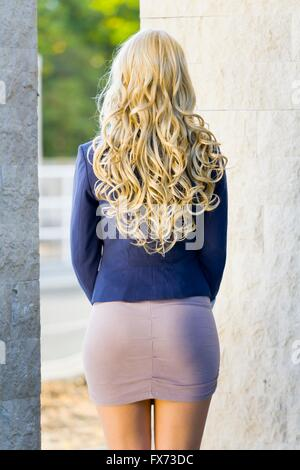 Curly hair young woman blonde rearview Blue suit mini short dress minidress curls hairdo beautiful attractive rear - Stock Photo