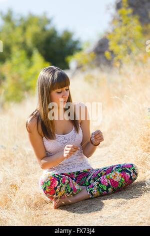 Teen-girl in colorful pants in nature sitting crossed-legs outdoors natural barefeet crossed legs isolated cross - Stock Photo