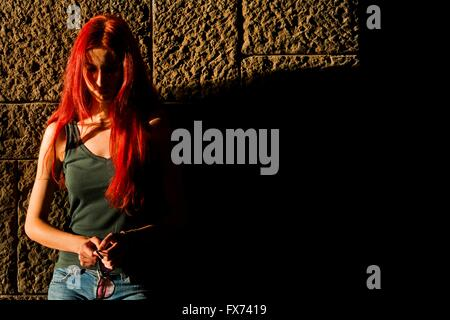 Red-haired woman with glasses in hands sunset sidelit sidelight - Stock Photo