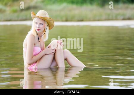 Teen girl blonde on beach outdoors nature natural environment single people looking back serious delightful wearing - Stock Photo