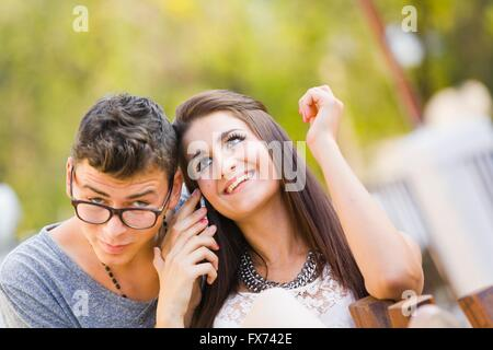 Girl boy listen to cellphone talk together responsive response smile smiling gossiping gossip hand hands sitting - Stock Photo