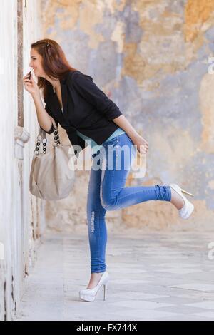 Fixing adjusting makeup denim pants balance balancing one leg heels handbag Black jacket outdoors stiletto stilettos - Stock Photo