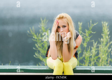 Young woman indifferent look outdoors hand touch headache pain head front frontal view eyescontact blonde hair Yellow - Stock Photo