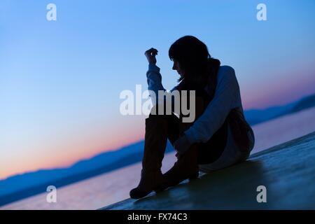 Sunset watching silhouette sitting seated near sea - Stock Photo