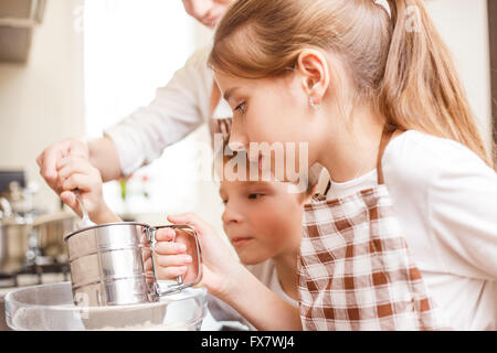 Family cooking background. Mum and children in the kitchen sieving flour - Stock Photo