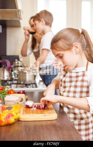 Teenage girl cooking together with her family in the kitchen. Caucasian girl cutting onion for salad Family cooking - Stock Photo