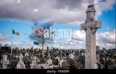 The Irish Tricolour and Starry Plough fly in the background of a Celtic Cross and graves in Milltown Cemetery in - Stock Photo