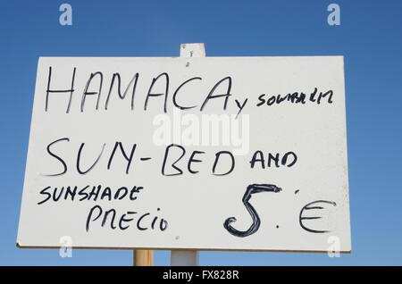 Sign announcing sun shade and sun bed in the beach of Marbella, Spain - Stock Photo