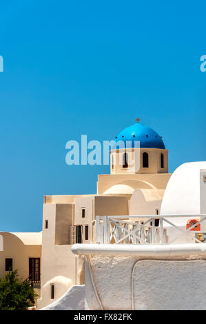 A view of one of the famous blue domed churches from Oia on the greek isle of Santorini. - Stock Photo