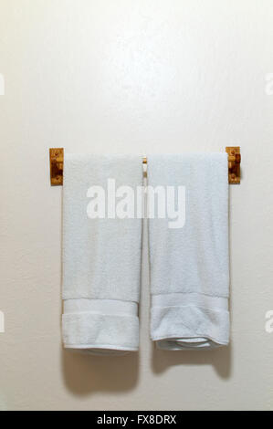Two white cotton terry cloth towels hanging on an off white wall from wooden rack,  with copy space - Stock Photo