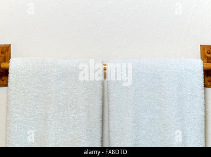 Two white cotton terry cloth towels hanging on an off white wall from wooden rack. - Stock Photo