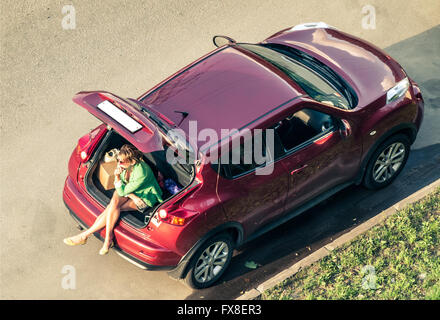 smoking woman sitting in luggage boot of hatchback - Stock Photo