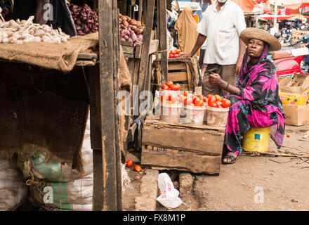 African woman wearing traditional clothes selling tomatoes in a local market. - Stock Photo