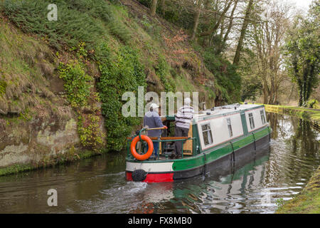 Narrowboat navigating a sandstone cutting on the Staffs and Worcester Canal near Wolverley, Worcestershire, England, - Stock Photo