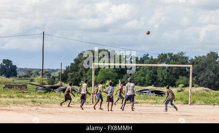 Batswana boys playing football, mostly with bare feet. Near Mohembo West, northern Botswana, southern Africa - Stock Photo