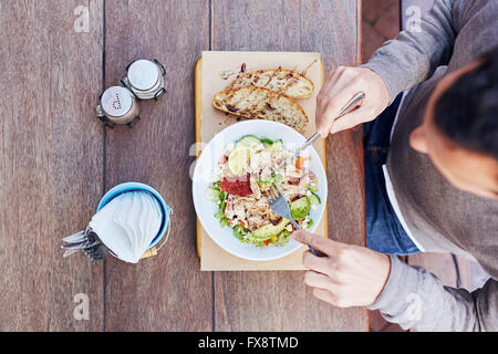 Person enjoying a fresh salad on their lunch break - Stock Photo