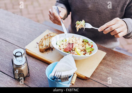 Man eating healthy chicken salad at a cafe - Stock Photo