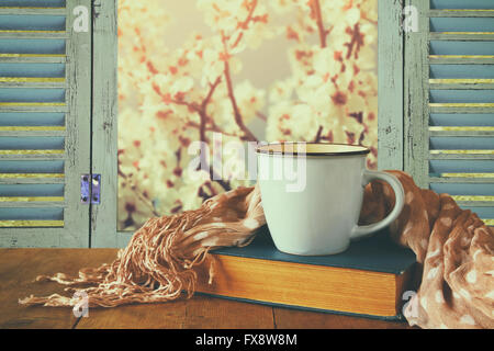 romantic scene of cup of coffee next to old book in front of countryside view outside of the old rustic window. - Stock Photo