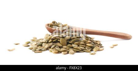 Wooden spoon over pumpkin seeds - Stock Photo