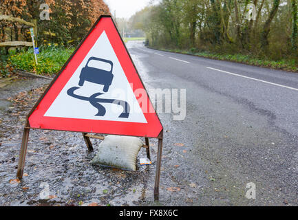 Slippery road triangular warning sign on a flooded road in the UK. - Stock Photo