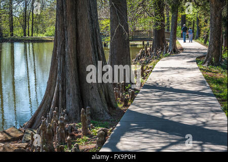 Senior couple holding hands on a leisurely stroll around the lake at Honor Heights Park in Muskogee, Oklahoma, USA. - Stock Photo