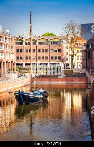 DUSSELDORF, GERMANY - MAY 3, 2013: Boat in harbor in Dusseldorf in Germany. Tourists nearby. Stock Photo
