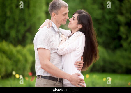Couple of lovers on a date in park, standing face to face, young man tenderly embracing his happy smiling girlfriend - Stock Photo