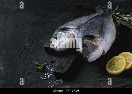 Two ready to cook raw bream fish with herbs and lemon on wooden cutting board over black textured background. - Stock Photo