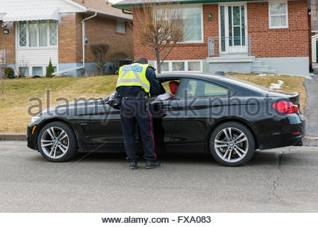 Toronto Police Service officer, giving a speeding ticket to a driver parked on the side of the road. - Stock Photo