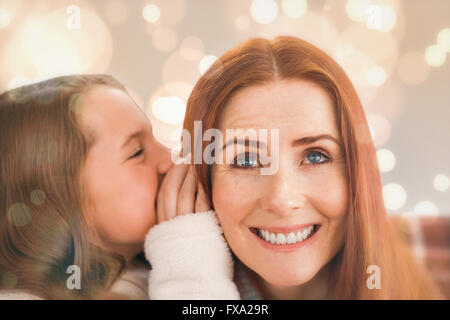 Composite image of mother and daughter telling secrets - Stock Photo