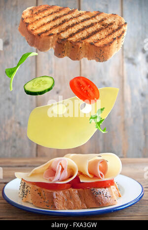 Sandwich ingredients falling into place onto a plate - Stock Photo