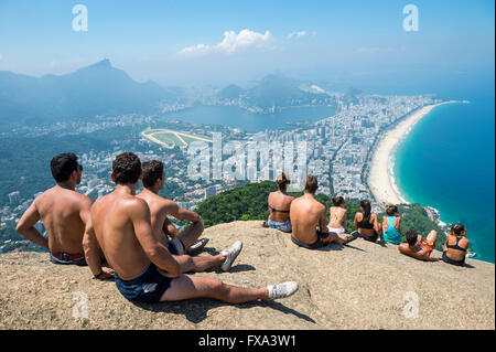 RIO DE JANEIRO - MARCH 9, 2016: Visitors take in the view of the city skyline after a hike to the top of Dois Irmaos - Stock Photo