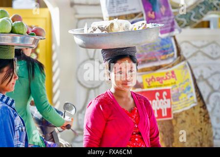 Local women carrying fruit and food on their heads, Kyauk Taw Gyi Pagoda at the foot of Mandalay Hill, Mandalay, - Stock Photo