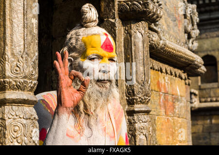 The portrait of a Sadhu, holy man, sitting in a doorway of Pashupatinath Temple, Kathmandu, Nepal - Stock Photo