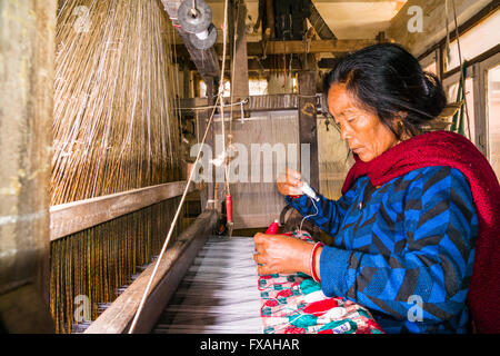 A woman is working on an old traditional loom, weaving the material for the Dhaka topi, the traditional nepali hats, - Stock Photo