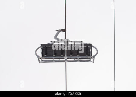 Low angle shot of skiers on the Retour Pendant chair lift at les Grand Montets, Chamonix, France - Stock Photo